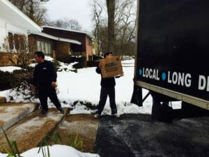Elite movers unload box winter snow