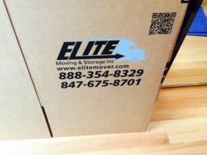 Elite Logo side of cardboard storage box on hardwood floor